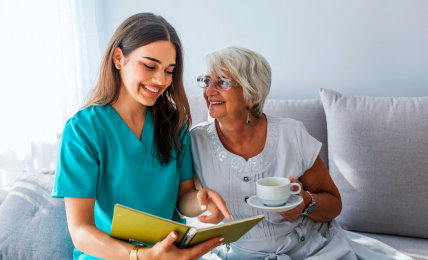 caregiver reading a book to the senior woman smiling