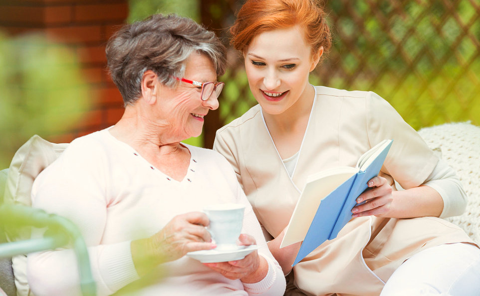 caregiver reading a book to the senior woman holding a cup of tea