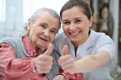 senior woman and female caregiver doing thumbs-up
